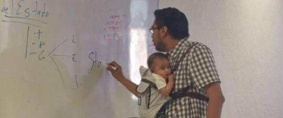 Professor segura bebê para que aluna possa assistir a aula