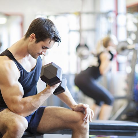 Handsome man lifting weight to tone his biceps in a sports gym. A woman is working out her back in the background. Fitness lifestyle, interior shot in a horizontal composition