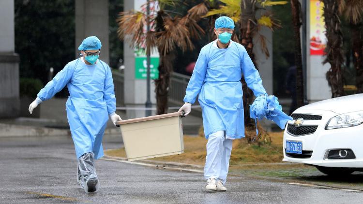 """pesquisadores carregam caixa no hospital jinyintan na china 1579657375162 v2 750x421 - OMS se corrige e eleva risco do coronavírus de """"moderado"""" para """"alto risco global"""""""