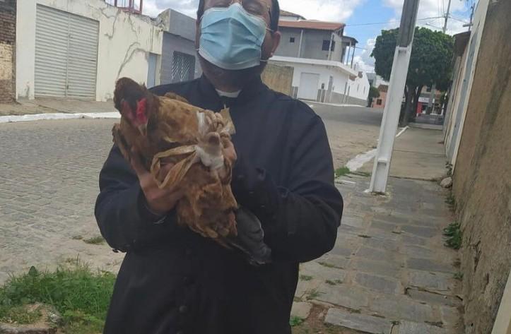 """galinha - Padre do Sertão da Paraíba surpreende fiéis e adota galinha de estimação chamada """"Rafinha"""""""