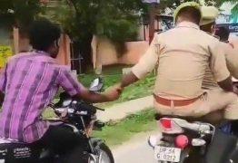Policial na garupa conduz detido a delegacia segurando a mão dele, que guia outra moto – VEJA VÍDEO