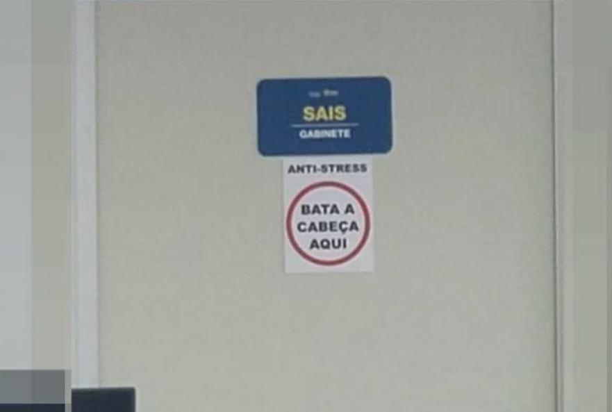 """Capturar 7 - Cartaz em sala de Secretaria de Saúde sugere que servidores aliviem o estresse: """"Bata a cabeça aqui"""""""