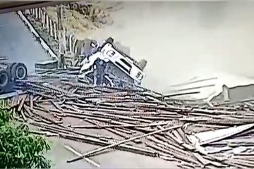 motorista ileso 360x240 - IMPRESSIONANTE: Motorista sai andando após caminhão tombar e espalhar carga de madeira pela pista - ASSISTA