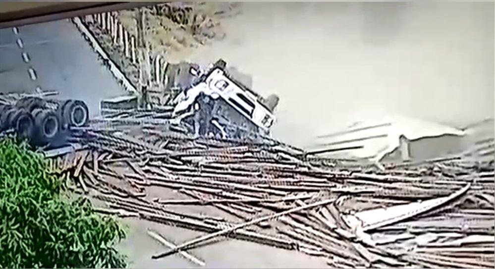 motorista ileso - IMPRESSIONANTE: Motorista sai andando após caminhão tombar e espalhar carga de madeira pela pista - ASSISTA