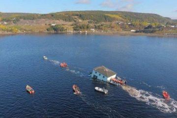 Casal transporta residência centenária através de lago para novo local de moradia