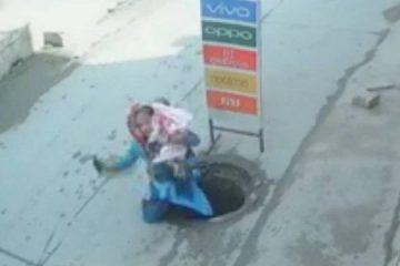 Mulher com criança no colo se distrai falando ao celular e cai em buraco em rua
